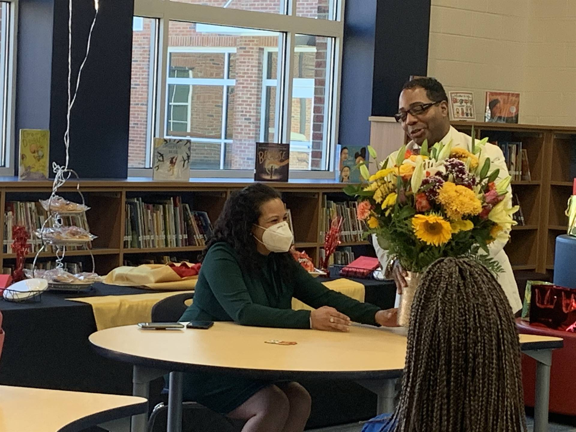 Dr. Berger presenting flowers to Supt.